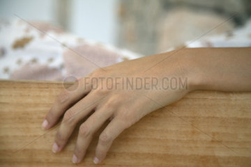 Woman's hand resting on table