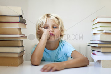 Boy sitting between two stacks of books with bored expression
