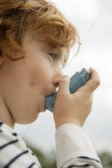 Boy using asthma inhaler
