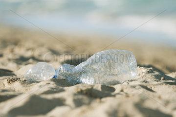Empty plastic bottle on beach  selective focus
