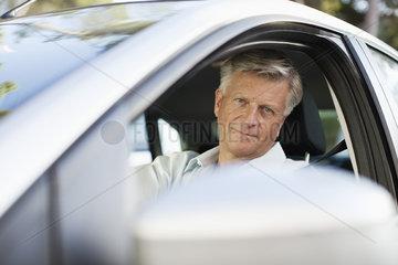 Man driving car  looking out window at camera