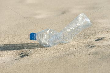 Empty plastic bottle on beach  close-up