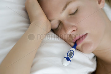 Young woman checking temperature with thermometer