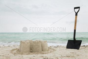 Shovel stuck in sand beside sand castle at the beach
