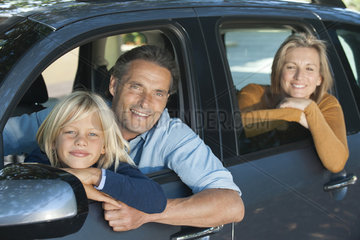 Family together in car  leaning out windows and smiling at camera