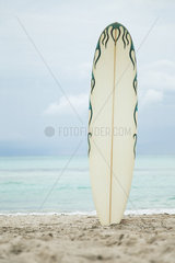 Surfboard stuck in sand at the beach