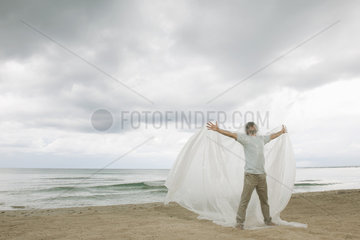 Man with arms outstretched trapped in plastic