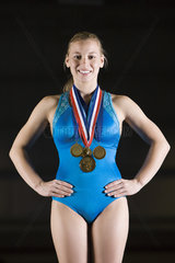 Female gymnast wearing gold medals  portrait