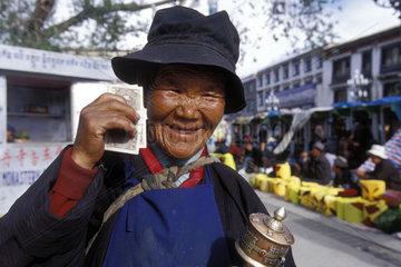 alte Tibeterin zeigt Geldscheine