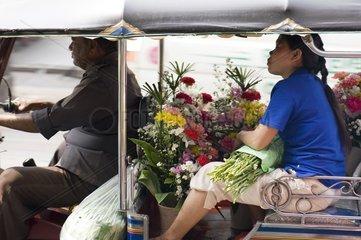 Frau transportiert Blumen im Tuk Tuk / Bangkok / Thailand / SUEDOSTASIEN-RE