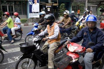 Mopedfahrer und Wahlplakat des Premierministers Abhisit Vejjajiva / Bangkok