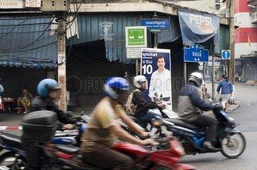 Mopedfahrer und Wahlplakat des Premierministers Abhisit Vejjajiva im chines