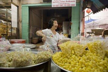 Suesswarenverkaeuferin an ihrem Stand im chinesischen Viertel / Bangkok / Tha
