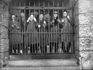 8 Maenner lachend hinter Gitter  1920