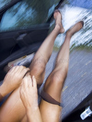 Frau im Auto sitzend zieht Strumpfhose an