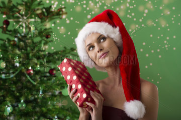 Woman wearing Santa hat and holding Christmas present  portrait