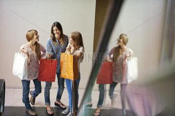 Young women carrying shopping bags  standing at bottom of escalator