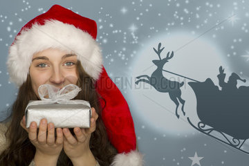 Young woman in Santa hat holding Christmas present  graphic of Santa's sleigh in background