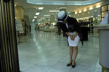elegant gekleidete Dame verbeugt sich