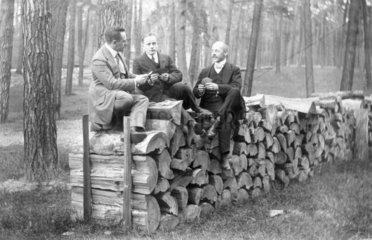 Maenner sitzen auf gestapeltem Holz