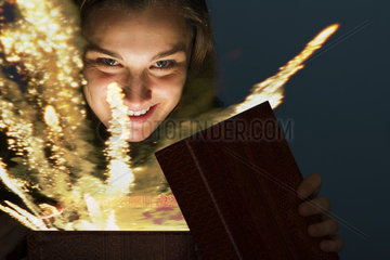 Young woman opening gift box containing glowing fireworks