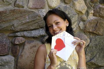 Frau zeigt Liebesbrief mit Herz