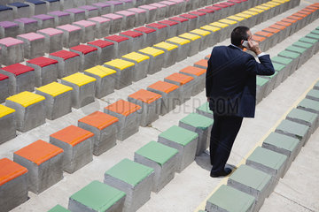Business executive using cell phone by rows of bleachers  rear view