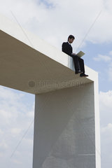 Businessman sitting on top of tall structure using laptop computer