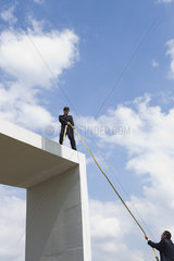 Businessman standing on top of tall structure  holding rope to help colleague