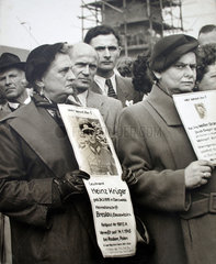 Frauen stehen und zeigen vermisste Maenner den Kriegsheimkehrern  1955