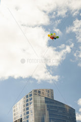 Bunch of balloons flying over office building
