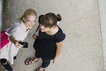 Young women posing for cell phone picture