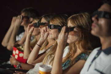 Audience in move theater putting on 3-D glasses