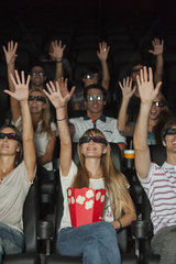 Audience wearing 3-D glasses in movie theater  arms reaching up