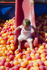 Toddler girl going down slide into ball pit on playground