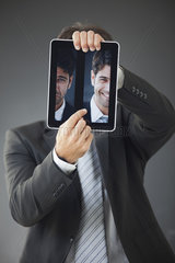 Man hiding behind images of himself frowning and smiling