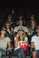 Audience wearing 3-D glasses in movie theater