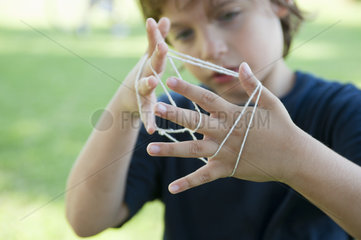 Boy playing cat's cradle  focus on hands