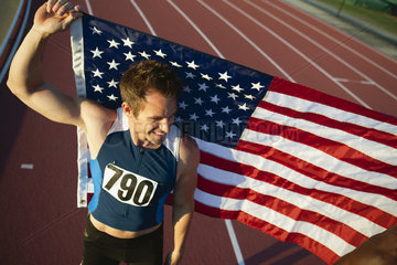 Runner holding up American flag after race