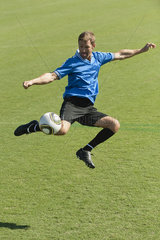 Soccer player kicking ball in midair