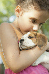 Girl kissing beagle puppy