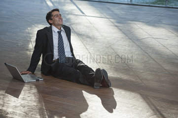 Businessman relaxing on deck with laptop computer