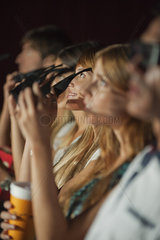 Audience in movie theater putting on 3-D glasses