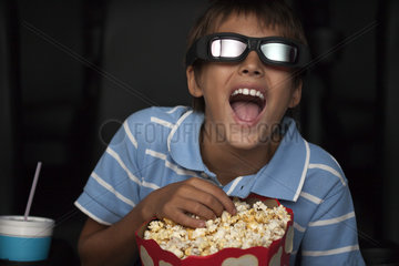 Boy laughing and eating popcorn during 3-D movie in theater
