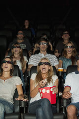 Audience wearing 3-D glasses in movie theater with shocked expressions on faces
