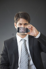 Man holding up smartphone displaying image of his own smile