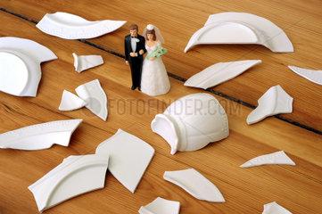 Figuren eines Hochzeitspaares stehen in einem Scherbenhaufen
