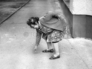 alte Frau bueckt sich