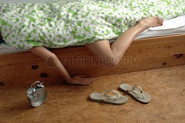 Frau mit Flip-Flops und Wecker neben dem Bett