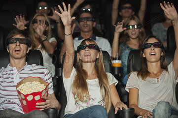 Audience wearing 3-D glasses in movie theater  arms reaching out